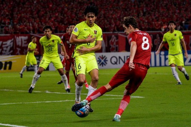 Shanghai SIPG's Oscar (R) shoots the ball as Urawa's Endo tries to block during AFC Champions League semi-final football match between Shanghai SIPG FC and Urawa Red Diamonds (Japan) in Shanghai on September 27, 2017.  / AFP PHOTO / CHANDAN KHANNA
