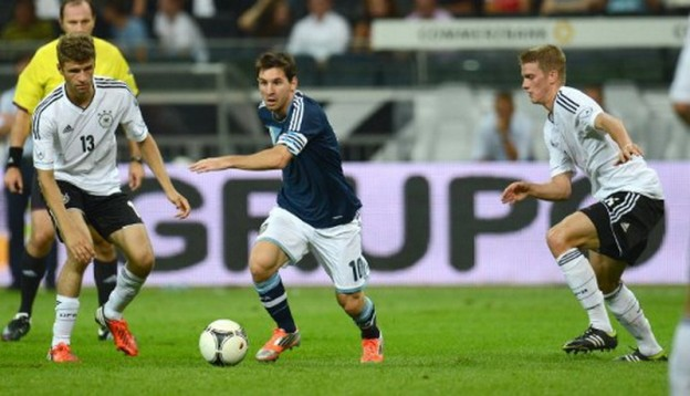 Argentina's striker Lionel Messi (L) vies for the ball with Germany's midfielder Thomas Mueller (L) and Germany's midfielder Lars Bender  during the friendly football match Germany vs Argentina on August 15, 2012 in Frankfurt am Main, western Germany . AFP PHOTO / PATRIK STOLLARZ / AFP PHOTO / PATRIK STOLLARZ